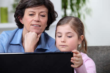50 55 years: Young girl surfing the Internet with her grandmother Stock Photo