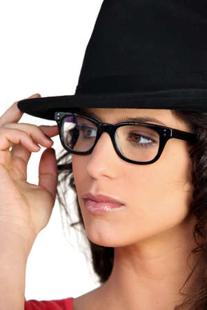 distant: Woman wearing a hat and thick-framed glasses