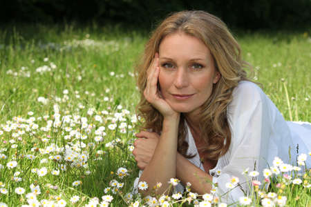 Woman laying down in field full of flowers photo
