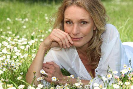 45 50 years: Woman lying in a grassy field