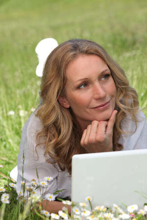 daydreaming: Woman on laptop in field Stock Photo