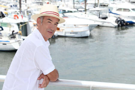 Older man in a straw panama hat standing by a marina photo