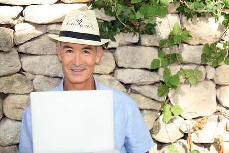 senior man doing computer outside photo