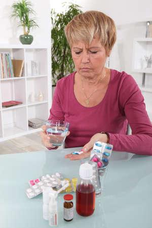 personas tomando agua: Una mujer gru�ona tomar sus pastillas