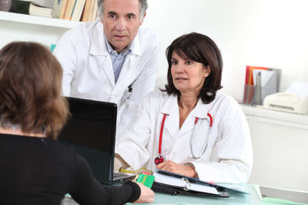 Doctors and patient sitting at a computer photo