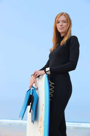 Woman stood in wetsuit with body-board photo
