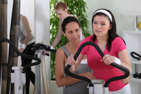 watch over: female riding a bike in the gym Stock Photo