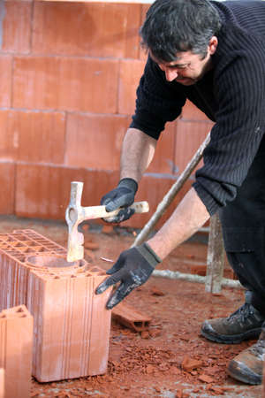 Builder hammering a brick photo