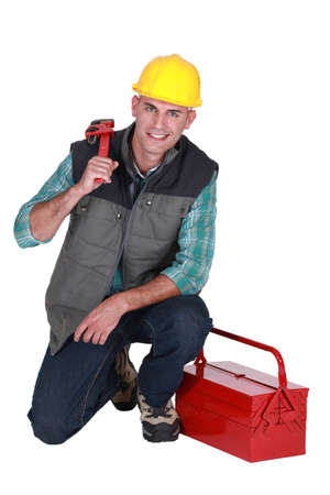 Smiling plumber with his toolbox on white background photo