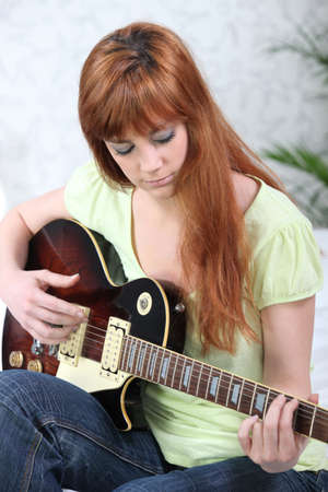 Ginger-haired girl playing guitar photo