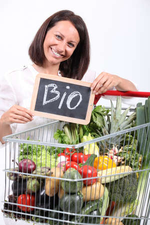 retailer: Woman with a trolley of organic vegetables Stock Photo
