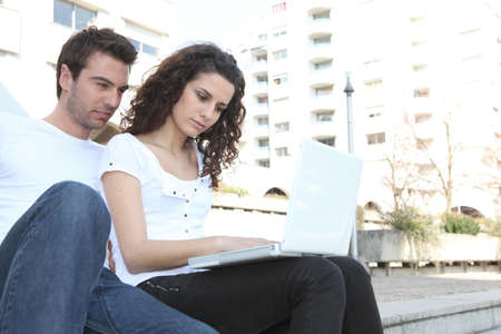 Couple using laptop computer outdoors photo