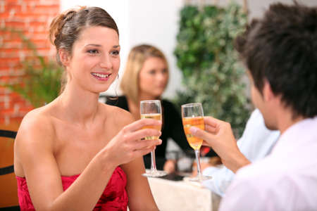 merriment: Couple with champagne glasses in restaurant