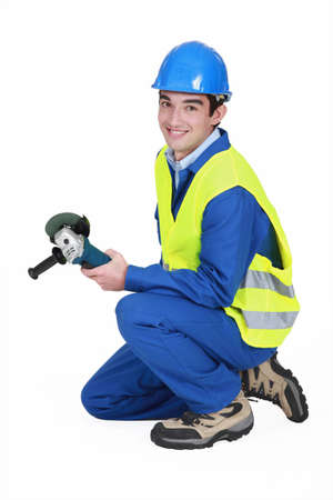 A male construction worker with a grinder. photo