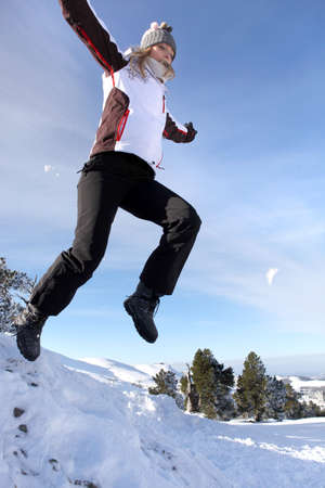 Woman jumping onto a pile of snow Stock Photo - 12219089