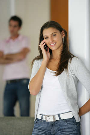 disrespect: man sulking while his girlfriend is talking on the phone