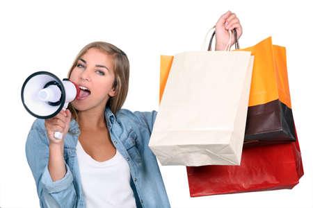 buen trato: Mujer sosteniendo bolsas de compras y gritando en un altavoz
