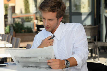 read news: Young man relaxing reading newspaper