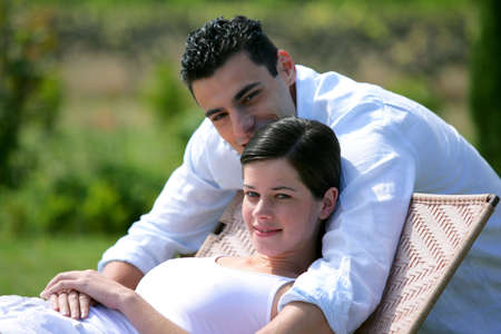 Pregnant woman and boyfriend in the garden photo