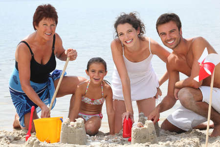 Family building sandcastles on the beach photo