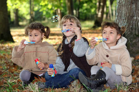 Young children blowing bubbles in the woods photo