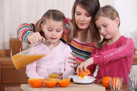 squeezing: Family squeezing fresh orange juice