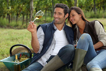 wine stocks: Couple taking a break from picking grapes Stock Photo