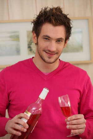 a young man pouring wine in a glass photo