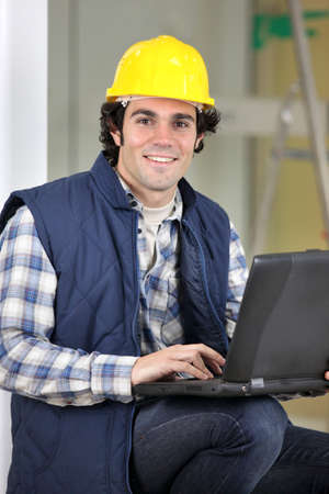 Builder sat with laptop Stock fotó