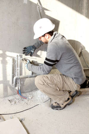 squat: Plumber working on a site