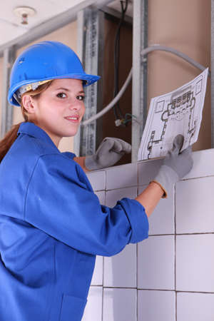 Female electrician looking at a diagram photo