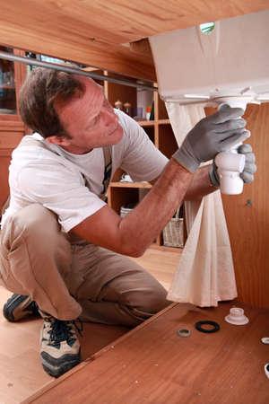 basin mountain: Plumber fixing a sink Stock Photo