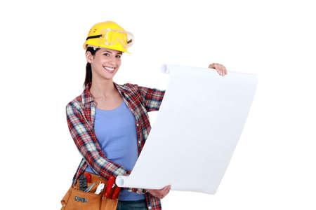 tradesperson: Tradeswoman examining a blueprint