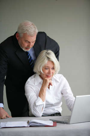 Older business couple looking at a laptop photo