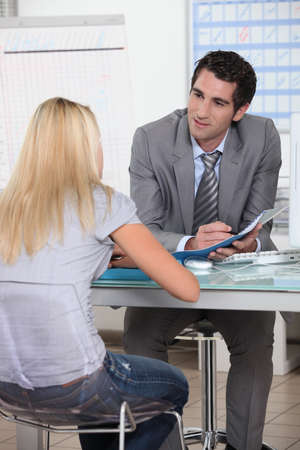 Young woman in interview with trainer photo