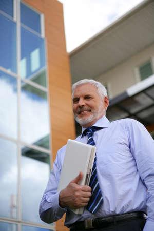 Senior businessman holding laptop outdoors photo