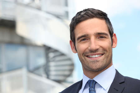 good looking man: Smiling business man standing outside office building