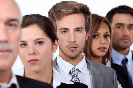 Zbliżenie twarzy grupy poważnych młodych biznesmenów i ich szefa starszych