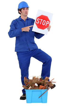Man stood holding stop sign by crate of refuge Stock Photo - 12246177