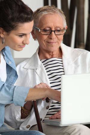 challenged: Elderly woman using laptop with carer