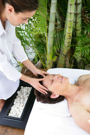 senior woman having a massage in a spa center photo