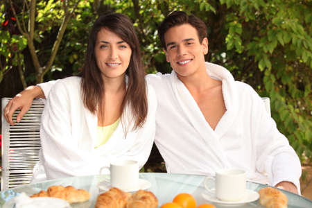 Young couple having breakfast outside photo