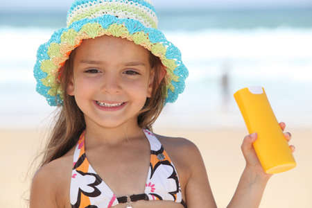 little girl on the beach with a sun cream photo