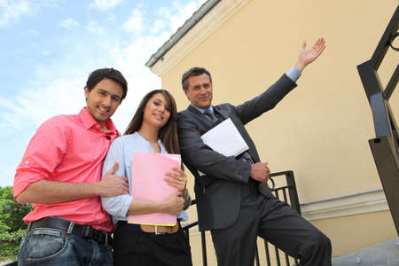 Couple with their realtor in front of their new house photo