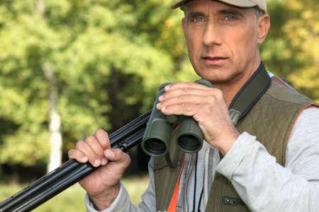 45 49 years: Hunter with a shotgun and pair of binoculars Stock Photo