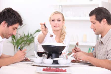 Three friends enjoying chocolate fondue photo