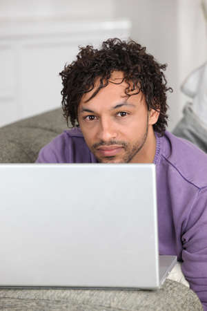 half-caste man with laptop in flat photo