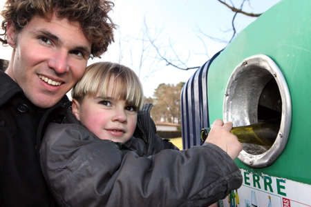 waste prevention: Father and son recycling glass bottles Stock Photo