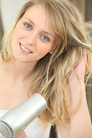 hairdryer: Blonde woman using a hairdryer Stock Photo