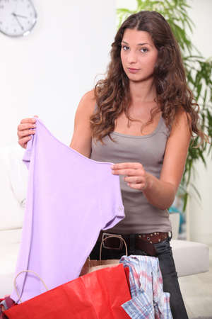 Woman looking at her shopping at home photo